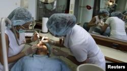 Dua dokter gigi merawat seorang pasien dari Amerika di klinik gigi di San Jose, Kosta Rika. (Reuters/Juan Carlos Ulate)