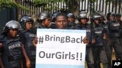 Picha ikionyesha kijana akiwa na bango la kampeni ya kuwaokoa wasichana waliotekwa na Boko Haram.