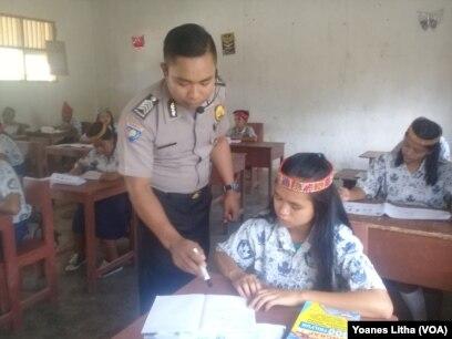 Brigadir Kepala Hans Lapanda mengajar Bahasa Inggris untuk kelas 8 di SD-SMP Negeri Satu Atap desa Bulili, Kecamatan Lore Selatan, Kabupaten Poso, Sulawesi Tengah, 27 April 2018. (VOA/Yoanes Litha)