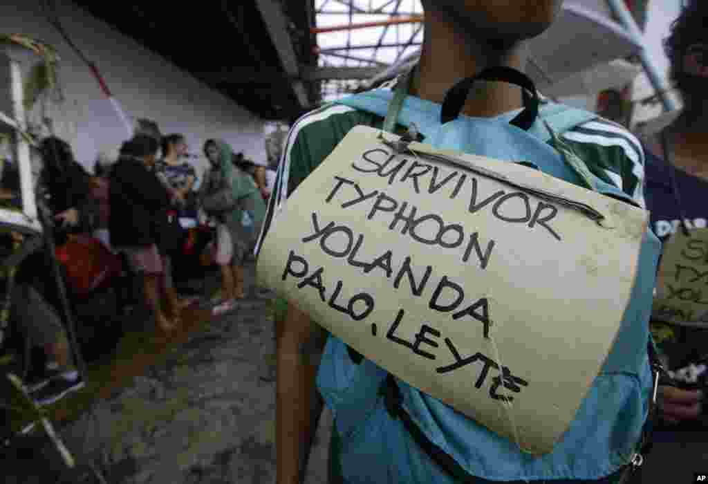 Typhoon survivors hang signs from their necks as they line up to try to board a C-130 military transport plane in Tacloban, Nov. 12, 2013.