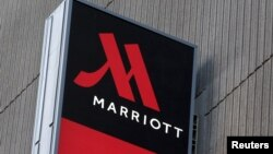 FILE - A sign advertises the New York Marriott Marquis in Manhattan. Marriott International bought Starwood Hotels and Resorts for $13.6 billion on Monday to create the world's biggest hotel chain, including three properties in Cuba.