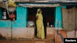 Child bride Krishna, 12, stands at a doorway into her compound in a village near Baran, in India's Rajasthan state, July 30 , 2011. Despite a law banning girls from marrying before they turn 18, the practice is deeply rooted in tradition and widely accepted in Indian society.