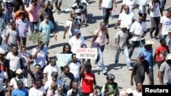 Manifestan ki te pran lari nan Pòtoprens pou yo pwoteste kont Prezidan Jovenel Moise nan dat 14 fevriye 2021.