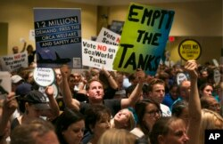 FILE - Opponents and supporters of SeaWorld's whale shows fill the room during a California Coastal Commission meeting in Long Beach, Calif., Oct. 8, 2015.