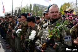 Armed pro-Russia rebels stand guard during celebrations to mark Victory Day in Donetsk, eastern Ukraine, May 9, 2014.
