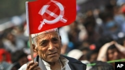 A supporter of Nepal Communist Party Maoist waves a flag during a mass rally in Katmandu, Nepal, June, 15, 2012.