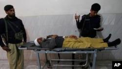 Cảnh sát Pakistan đứng bên cạnh đồng nghiệp bị thương tại bệnh viện Lady Reading ở Peshawar.