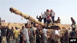 Chiến binh NTC ăn mừng sau khi chiếm được một chiếc xe tăng từ lực lượng thân Gadhafi ở thị trấn Sirte, ngày 20/9/2011