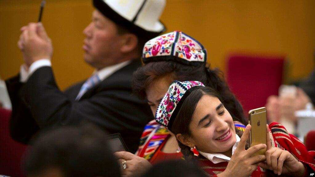 """2016年3月8日,中国人大会议期间新疆代表在北京人民大会堂的用智能手机拍照。他们的手机是否被监控?国际人权组织""""人权观察""""说很多新疆穆斯林的手机受到监视。"""