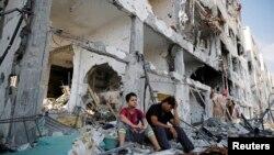 Người Palestine ngồi trên đống đổ nát tại thị trấn Beit Hanoun, sau các vụ không kích của Israel vào phía bắc Dải Gaza, ngày 5/8/2014.