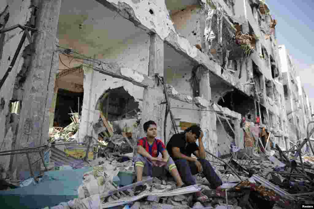 Palestinians sit on the remains of their destroyed homes after returning to Beit Hanoun, which witnesses said was heavily hit by Israeli shelling and air strikes during the Israeli offensive, in the northern Gaza Strip, Aug. 5, 2014.