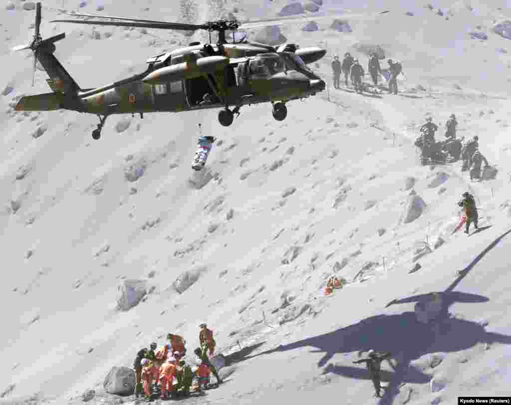 A hiker is lifted by a rescue helicopter of Japan Self-Defense Force (JSDF) during a rescue operation at Mount Ontake, which straddles Nagano and Gifu prefectures, central Japan, Sept. 28, 2014.