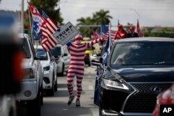 2020年11月1日迈阿密特朗普总统支持者穿国旗主题长袜走在两排汽车之间。
