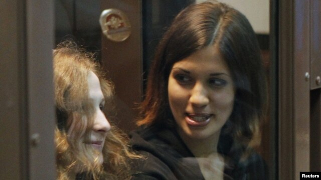 Band members Maria Alyokhina, left, and Nadezhda Tolokonnikova in a glass-walled cage before a Russian court hearing, Moscow, October 10, 2012.