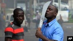 Un immigrant armé d'une machette, aperçu sur une rue au cours d'affrontements avec la police et des xénophobes qui ont attaqué les propriétaires de magasins étrangers dans le centre-ville à Durban, Afrique du Sud, mardi 14 Avril 2015.