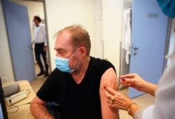 A man receives a Chinese made Sinopharm COVID-19 vaccine in Budapest, Hungary on Wednesday, Feb. 24, 2021. China is providing the vaccine to countries such as Serbia and Hungary -- a significant geopolitical victory in Central Europe and the Balkans, wher