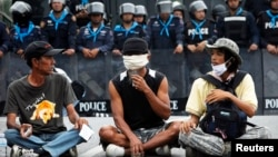 Anti-government protesters sit in front of a line of policemen outside Government House in Bangkok, Oct. 10, 2013.