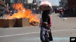 FILE: A woman and child pass a fire set alight during a protest in Harare, Friday, Aug. 26, 2016. (AP Photo)