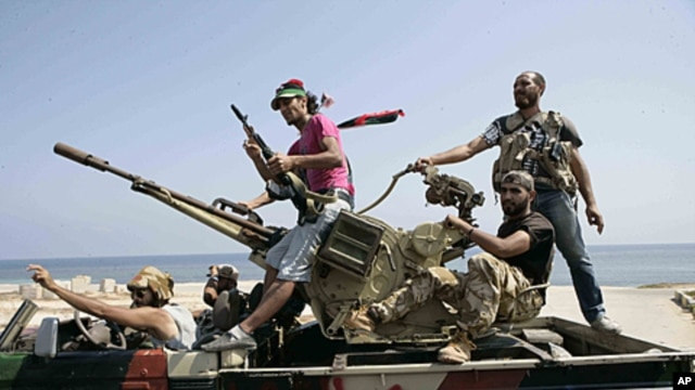 Rebel fighters search for Libyan leader Moammar Gadhafi's forces in Tripoli, August  26, 2011