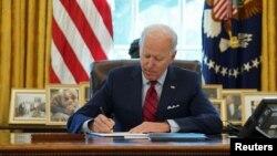 រូបឯកសារ៖ ប្រធានាធិបតីសហរដ្ឋអាមេរិកលោក Joe Biden ចុះហត្ថលេខាលើបទបញ្ជានីតិប្រតិបត្តិមួយ នៅសេតវិមានក្នុងរដ្ឋធានីវ៉ាស៊ីនតោន សហរដ្ឋអាមេរិក កាលពីថ្ងៃទី២៨ ខែមករា ឆ្នាំ២០២១។