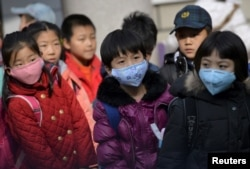 FILE - Schoolchildren wear masks as they leave school early at noon due to heavy air pollution, at a primary school in Shenyang, Liaoning province, Nov. 13, 2015.