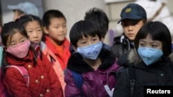 FILE - Schoolchildren wear masks to filter out particulate matter in Shenyang, Liaoning province, China, Nov. 13, 2015.