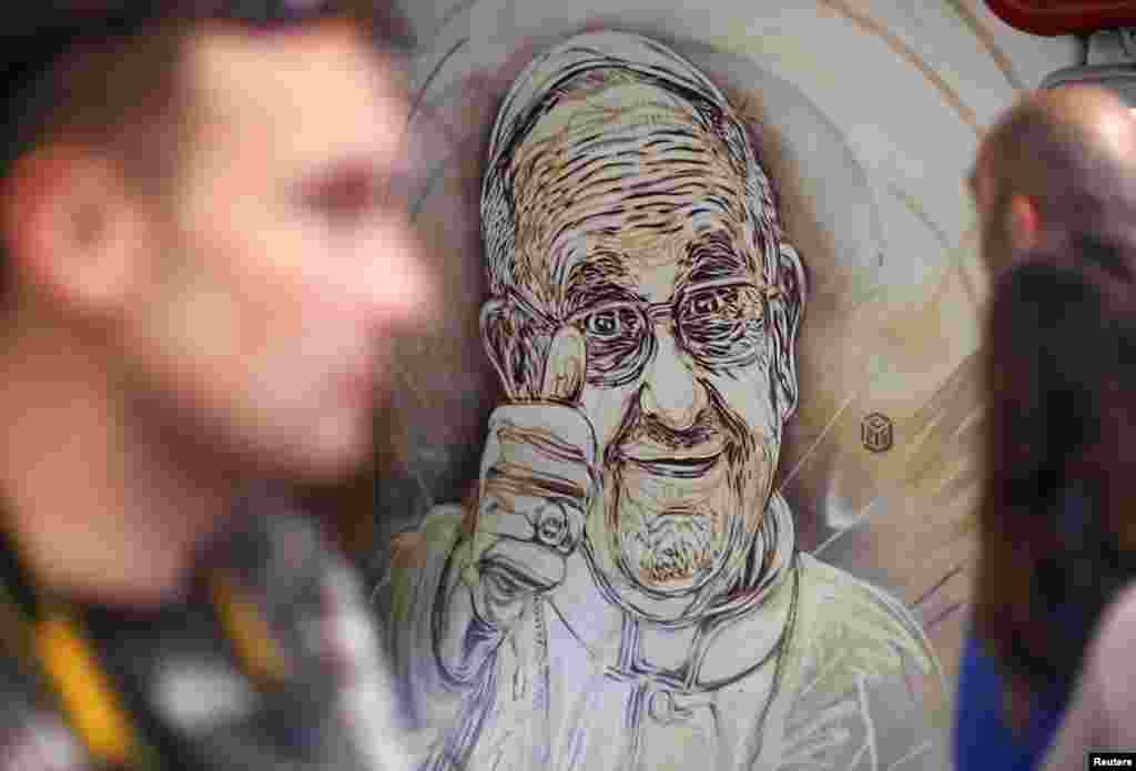 People pass a mural by French street artist Christian Guemy, also known as C215, which depicts Pope Francis giving the thumbs-up sign, in a subway station in Rome. The mural is near a ticket booth at the subway stop at the Spanish Steps, one of the capital's most popular tourist stops.