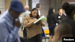 FILE - Malana Long fills out a job application during a job fair for the homeless at the Los Angeles Mission in the Skid Row area of Los Angeles, California, June 4, 2015. The number of Americans filing new claims for unemployment benefits fell more than expected last week, pointing to a tightening labor market.