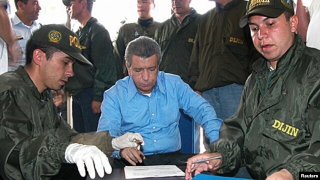FILE - Colombian police fingerprint the former boss of the powerful Cali drug cartel, Miguel Rodriguez Orejuela, before being extradited to the United States at Palanquero military Base in Puerto Salgar, March 11, 2005.