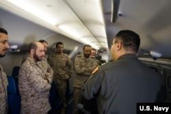 """美国海军资料照片:分配入美国海军巡逻第5中队的战术协调员杨帆(右,音译)上尉在P-8A""""海神""""反潜飞机上向沙特皇家海军人员展示飞机的系统(2018年3月1日)。"""