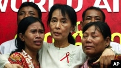 Aung San Suu Kyi (C) comforts crying HIV/AIDS infected people during a visit to the National League for Democracy (NLD) party headquarters to mark World AIDS Day in Yangon December 2, 2010. REUTERS/Soe Zeya Tun (MYANMAR - Tags: HEALTH POLITICS IMAGES OF