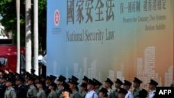 资料照:香港各种警察部队成员站在港版国安法广告牌前 (2020年7月1日)