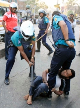 A policeman uses a baton on an activist of Jamaat-e-Islami, Bangladesh's biggest Islamist party, during a clash at Jatrabari in Dhaka, Feb. 28, 2013.