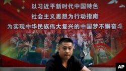 一名男子走过北京街头宣传习近平指示的各族人民大团结中国梦的广告牌。(20218年9月11日)