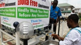 A man washes his hands at a tap outside the Green Pharmacy, Area 8, in Abuja, Sept. 1, 2014.