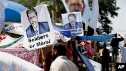 A supporter of Egypt's Islamist President Mohamed Morsi in front pictures of Morsi at Nasr City, where protesters have installed their camp and hold their daily rally, in Cairo, Egypt, July 25, 2013.