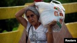 Một người dân Venezuela đang xách túi nhu yếu phẩm mua được từ Colombia, 10/7/2016.