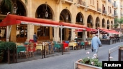 People walk past empty restaurants in downtown Beirut, Nov. 20, 2012.