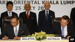 Malaysian Home Minister Hishammuddin Hussein, foreground left, and Australian Immigration Minister Chris Bowen, foreground right, sign documents to swap refugees between the two countries, in Kuala Lumpur, Malaysia, July 25, 2011