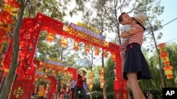 FILE - Pen Pu (center) and Chelsea Peng play with their three-year-old son Dore Peng at the Chinese Garden of Friendship in Sydney, Australia, 2015. (AP Photo/Rick Rycroft)