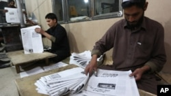 FILE - Afghan workers arrange copies of the 8AM daily newspaper in Kabul, Afghanistan.