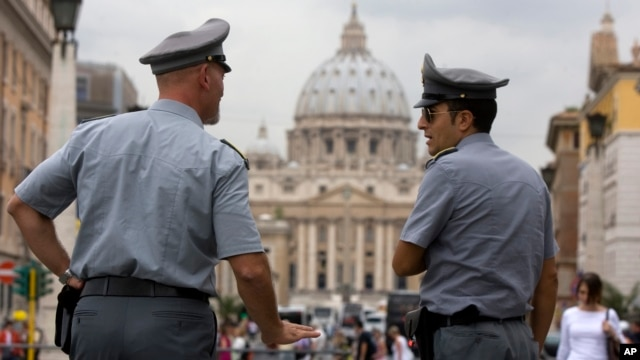 FILE - Italian financial police officers talk to each other in front of St. Peter's Square at the Vatican, Sept. 2010.