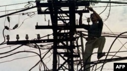 Một người thợ đang mắc dây điện trên một con đường ở Hà Nội