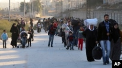 This Nov. 27, 2016, photo provided by the Rumaf, a Syrian Kurdish activist group, shows people fleeing rebel-held eastern neighborhoods of Aleppo into the Sheikh Maqsoud area that is controlled by Kurdish fighters.