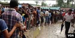 Rohingya refugees line up for water at a new settlement near Uchi Prank, Bangladesh.