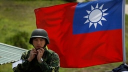 资料照:台湾旗帜前一名士兵整理自己的头盔。
