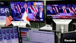An employee of a foreign exchange trading company looks at monitors showing U.S. President elect Donald Trump speaking on TV news in Tokyo, Japan, Nov. 9, 2016.