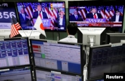 FILE - An employee of a foreign exchange trading company looks at monitors showing U.S. President elect Donald Trump speaking on TV news in Tokyo, Japan, Nov. 9, 2016.