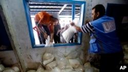 8月6日,巴勒斯坦人在加沙市一个难民营的联合国食品发放中心的窗子前排队,领取食物。