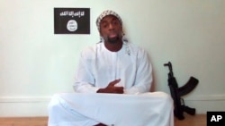 FILE - Amedy Coulibaly, killed by police after taking hostages at a Paris kosher market, appears in a video posted online by militants two days later, on Jan. 11, 2015. Spanish police have arrested a man suspected of supplying Coulibaly with a gun.